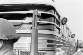 Freedom riders peer from bus windows during a stop.