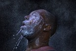 A man is doused with milk and sprayed with mist after being hit by an eye irritant from security forces trying to disperse demonstrators in Ferguson, Missouri August 20, 2014. (REUTERS/Adrees Latif)