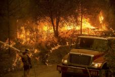 A firefighter sprays water on a backfire while battling the Butte Fire near San Andreas.