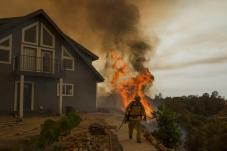 A firefighter works to save a residence from the Butte Fire.