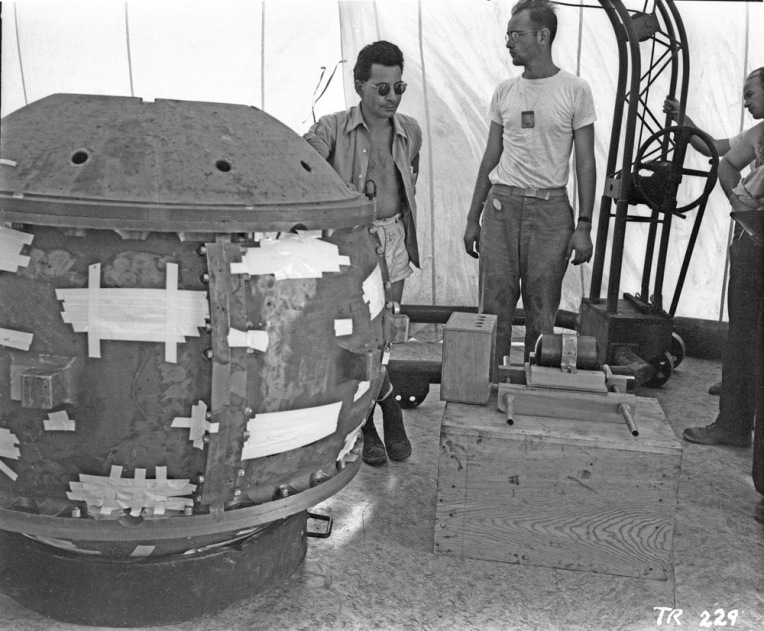 """Manhattan Project scientists Louis Slotin and Herb Lehr help assemble the Trinity """"Gadget""""—the world's first atomic bomb—in 1945. Once you know what you're looking at, the big round bomb on the left is less evocative than the small, cylindrical """"slug"""" sitting on the wooden crate on the right. That slug is made of uranium-238, and it's heavy—hence the two-handled carrying mechanism. The uranium slug carried the plutonium sphere that ultimately reached """"critical mass"""" and caused Trinity's chain reaction—a nuclear explosion. Photograph courtesy Los Alamos National Laboratory Archives. (CC BY-NC-ND 2.0)"""